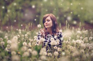 img of woman in dandelion field