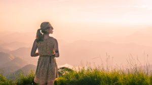 Girl looking out at a ledge from a hillside