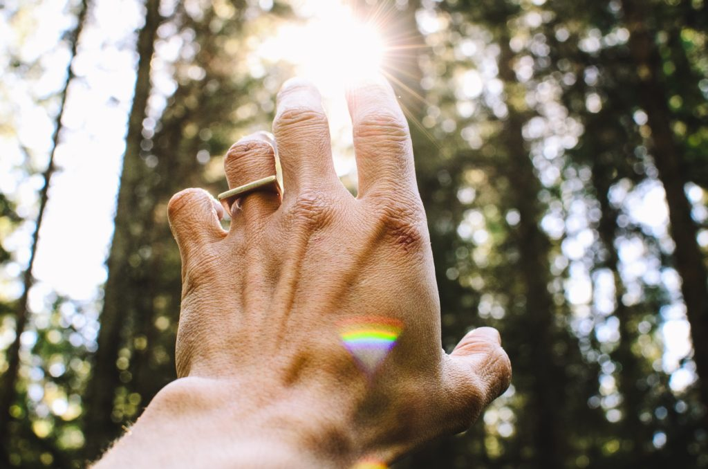 5 ways reiki helped me improve my life. Image of reiki hand reaching up to point of sunlight, natural energy shows Reiki healing energy